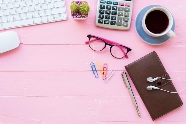 ピンクの木製の背景にワークスペースとオフィスアクセサリーを備えたオフィステーブル。