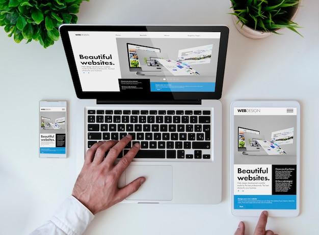クールなレスポンシブデザインのウェブサイトを示すタブレット、スマートフォン、ラップトップを備えたオフィスの卓上