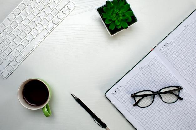 Офисные инструменты и чашка кофе на столе