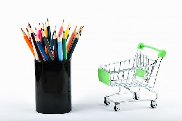장바구니에 office 도구입니다. 온라인 쇼핑 개념. 장바구니와 연필 화이트