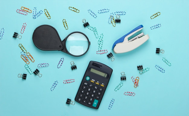 Office tools, stationery. stapler, calculator, magnifier, paper clips on a blue pastel.