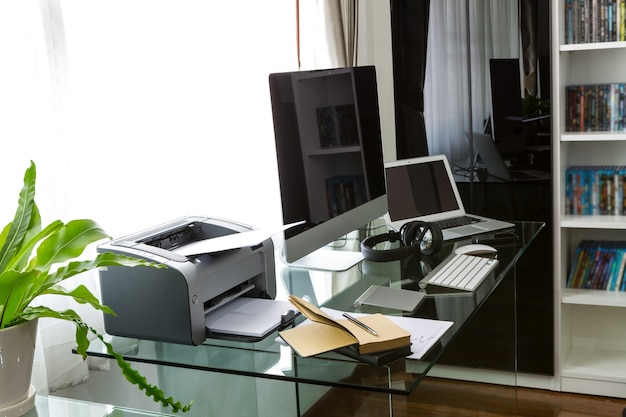Office with a computer and a glass table