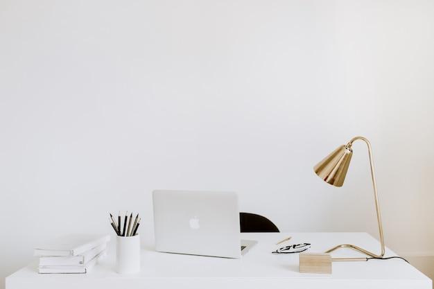 ノートパソコン、ランプ、ノートブックを備えたオフィス。ホワイトワーキングスタディキャビネット