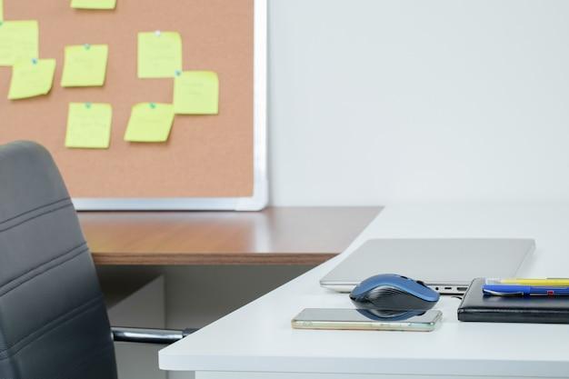 노트북, 전화, 책상, 보드 및 검은 색 좌석이있는 사무실