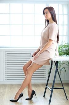 Office woman in beige dress and black stilettos