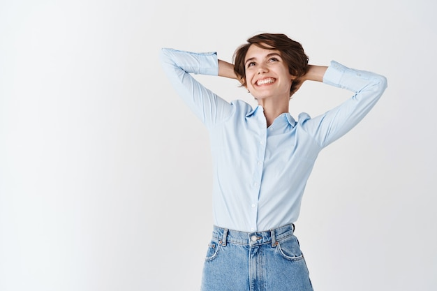 Office woman dreaming of vacation, looking relaxed up and smiling, holding hands behind head and resting from work, standing on white wall