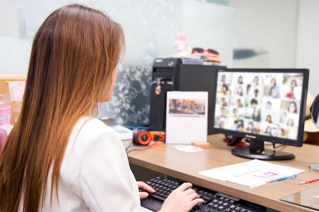 사무실 여자는 온라인 회의를 위해 데스크톱 컴퓨터를 사용하고 있습니다.