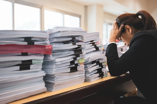 Office woman worker is distressed with a lot of paperwork on her desk.
