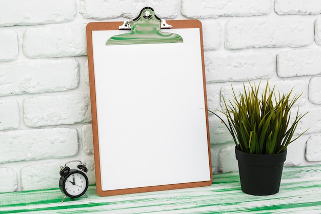 Office wooden clipboard standing against white brick wall, copy space