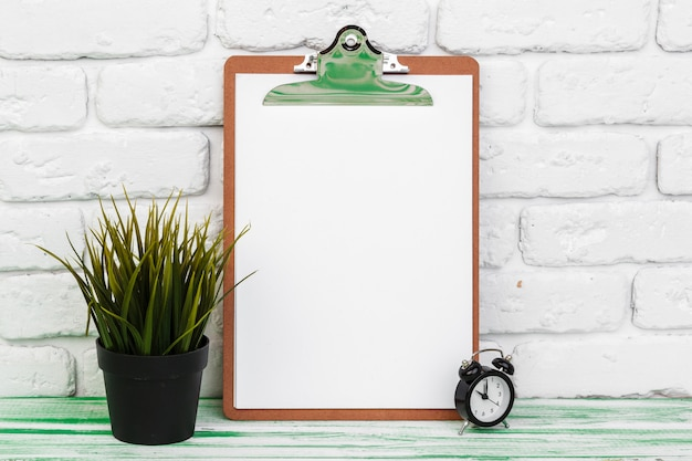 Office wooden surface clipboard standing against white brick wall