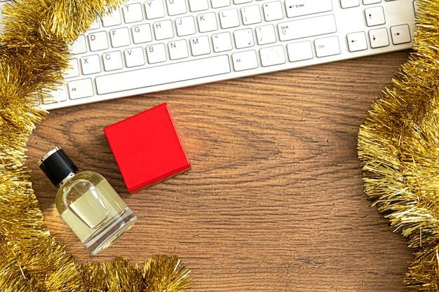 香水、赤い箱の贈り物、および金の見掛け倒しが付いているオフィスの木製のテーブル。上面図。