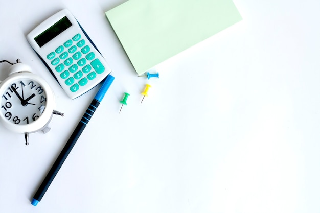 Office work, clock, calculator, note paper, paper clips, pen and coffee on white background, copy space