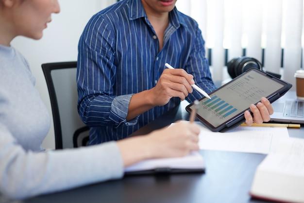 Концепция работы в офисе бизнесмен, показывающий гистограмму, представляющую интересную информацию о новой деловой тенденции своему коллеге.