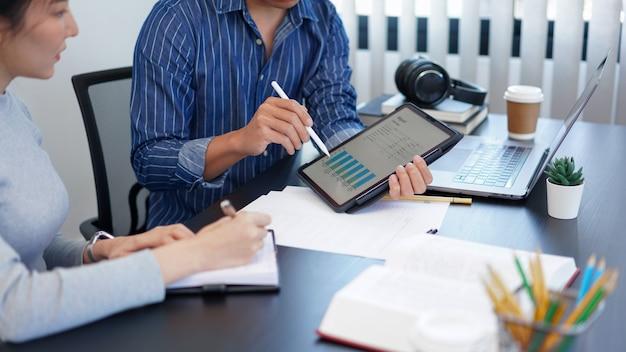 オフィスワークのコンセプトは、新しいビジネストレンドの興味深い情報を同僚に提示する棒グラフを示すビジネスマンです。