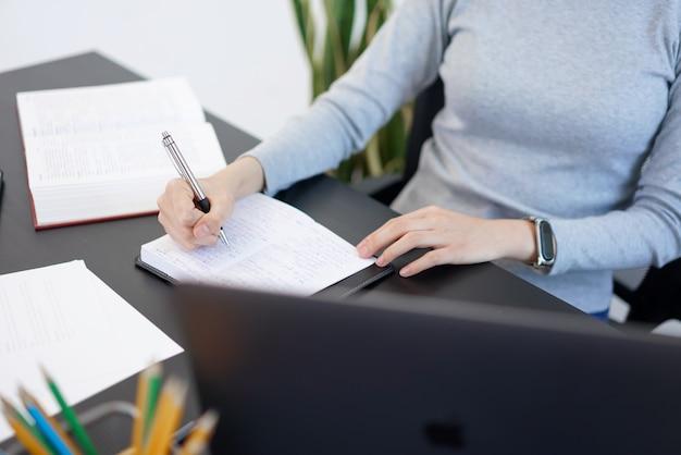 オフィスワークのコンセプトは、女性秘書が重要なビジネス情報について聞いていることを書き、メモをとることです。