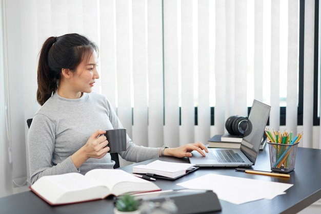 Office work concept a female secretary holding a cup of coffee relaxingly doing her job.