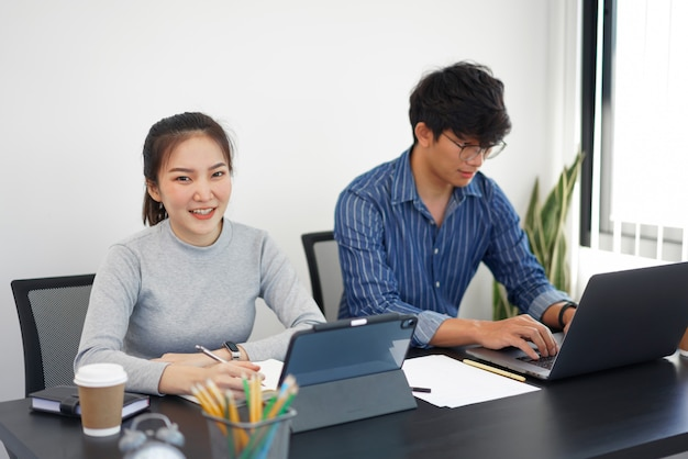 オフィスワークコンセプトオフィスで2杯のコーヒーを使ってデバイスに取り組んでいる2人のビジネスパーソン。