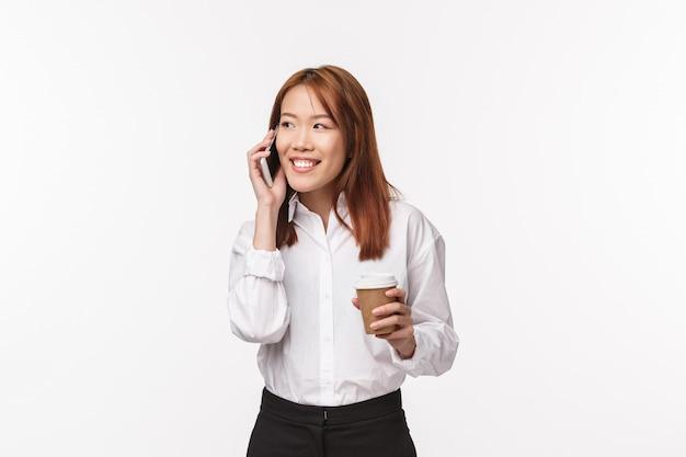 Офисная работа, люди и бизнес-концепция. портрет милой азиатской девушки, пьющей кофе и говорящей по телефону с довольной, удивленной улыбкой, беззаботно разговаривающей на перерыве на белой стене