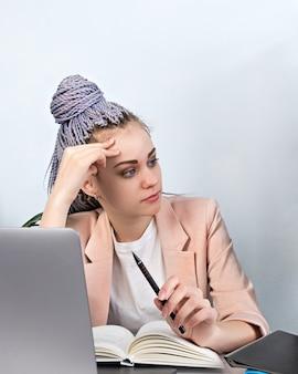 사무, 피곤, 과로. 분홍색 재킷과 kanekolon 머리띠를 입고 사무실에서 노트북을 들고 피곤 된 젊은 현대 여자의 초상화. 두통, 앉아있는 생활 방식