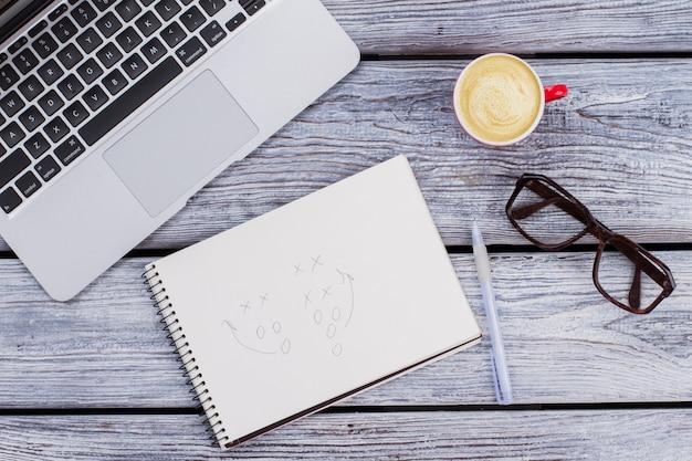 Аксессуары офисного работника и пустой блокнот. ноутбук с чашкой кофе и очками на белом деревянном столе.
