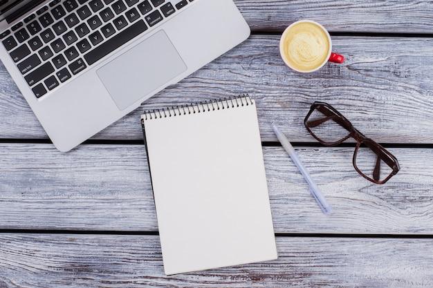 Плоская планировка принадлежностей офисного работника. пустой блокнот с компьтер-книжкой, очками и ручкой на сером деревянном столе.