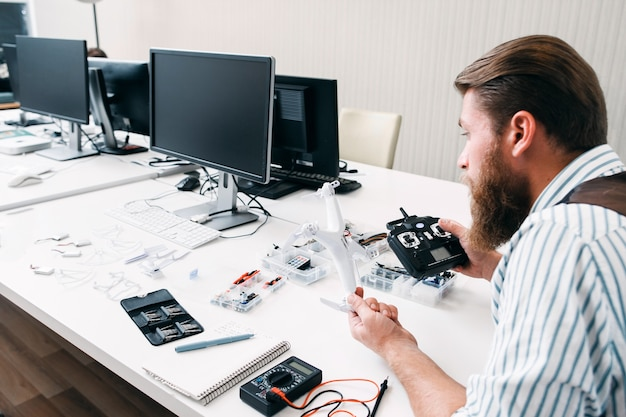 Office worker assembling drone at work. bearded man sitting in open space with quadrocopter and tools, and constructing electronic toy