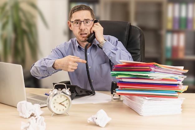 たくさんのフォルダーとしわくちゃの紙を持ってオフィスの彼の机にいるサラリーマン