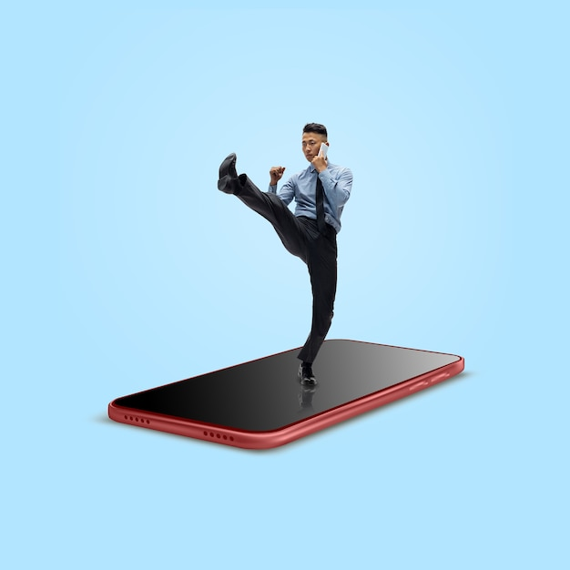 Office worker businessman fighting on the surface of smartphones screen isolated on background