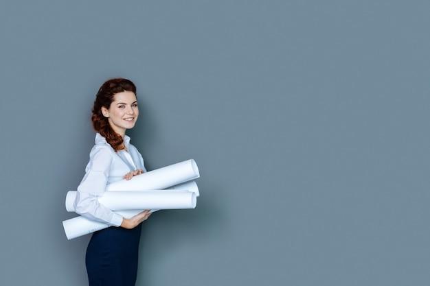 Офисный рабочий. веселая позитивная привлекательная женщина улыбается и держит чертежи во время работы