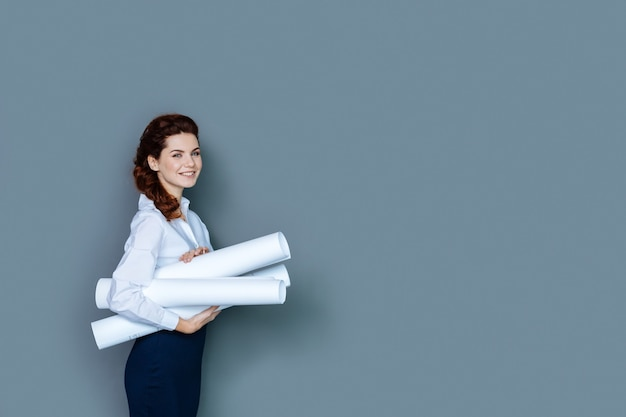Office worker. cheerful positive attractive woman smiling and holding blueprints while being at work