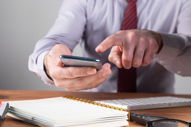 Офисный работник щелкает по телефону.