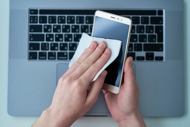 Офисный работник дезинфицирует и очищает телефон с помощью антибактериальных влажных салфеток для защиты от вспышки коронавируса