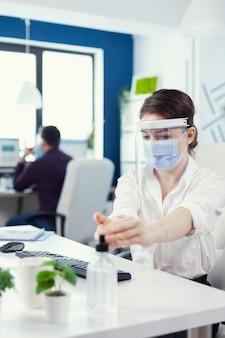 Impiegato che segue le precauzioni di sicurezza durante la pandemia globale con coronavirus che applica disinfettante. imprenditrice nel nuovo normale posto di lavoro che disinfetta mentre i colleghi lavorano in background.