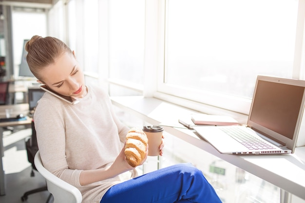 회사원은 점심을 먹습니다. 소녀는 광고 음료를 먹기 위해 크루아상과 커피 한 잔을 가지고 있습니다. 또한 여자는 전화로 이야기하고 있습니다. 그녀는 손이 바빠서 머리와 어깨 사이에 전화를 넣어