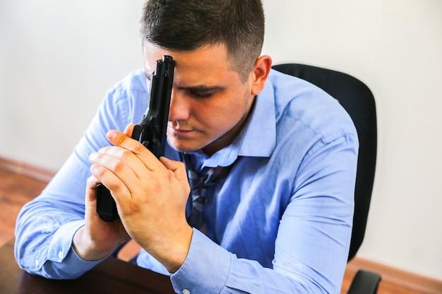 회사원은 손에 총을 들고 있습니다. 업무 스트레스로 인한 자살. 우울증 또는 소진. 끔찍한 생활 상황. 책상에 노트북 근처 남자입니다.