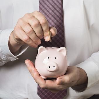 흰 셔츠와 넥타이에있는 회사원은 돼지 저금통 개인 개발 개념에 동전을 넣습니다.