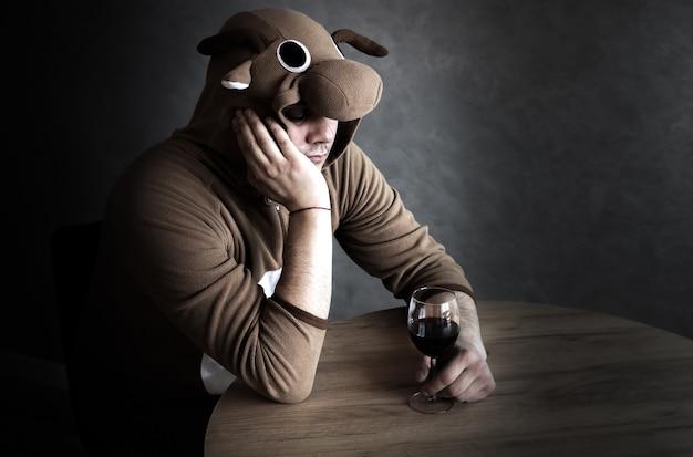 소의 코스프레 의상을 입은 회사원. 와인 한 잔 근처에 재미있는 동물 잠옷을 입은 남자. 알코올 중독자, 실직, 실업 개념, 경제 위기. 우울증과 알코올 중독.