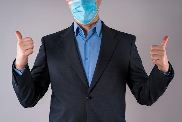 Офисный работник в защитной маске на серой стене
