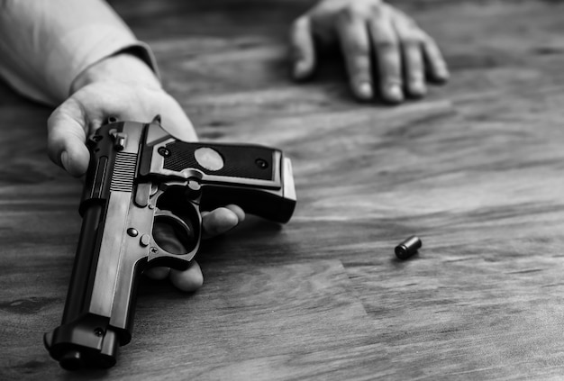 회사원은 손에 총을 들고 바닥에 누워 있습니다. 업무 스트레스로 인한 자살. 우울증 또는 소진. 끔찍한 생활 상황. 흑백 사진입니다.