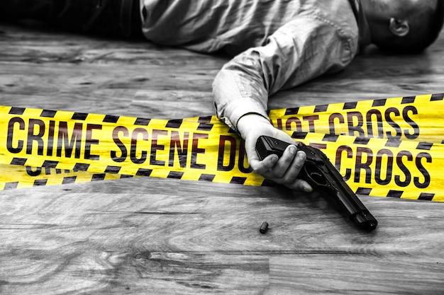 サラリーマンは銃を手に持って床に横になっています。仕事のストレスによる自殺。うつ病または燃え尽き症候群。ひどい生活状況。クロスサインしないでください。