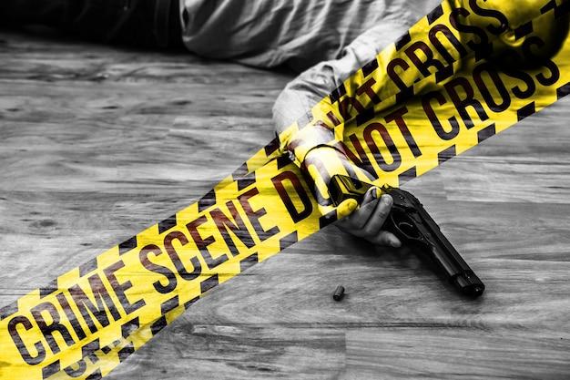 회사원은 손에 총을 들고 바닥에 누워 있습니다. 업무 스트레스로 인한 자살. 우울증 또는 소진. 끔찍한 생활 상황. 기호를 교차하지 마십시오.
