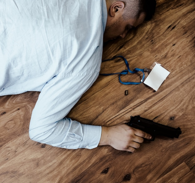 회사원은 손에 총을 들고 바닥에 누워 있습니다. 업무 스트레스로 인한 자살. 우울증 또는 소진. 끔찍한 생활 상황. 책상에 노트북 근처 남자입니다.