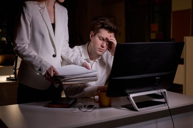 회사원 남자는 여성 이사의 지시와 작업을 받는 데 지쳤고, 많은 서류와 지시 또는 지시를 받습니다. 금융, 사무실, 브레인스토밍, 마감 개념