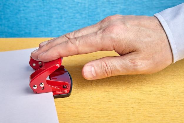 Офисный работник пробивает отверстия в листе бумаги, используя стальной дырокол, крупный план руки с белым рукавом.