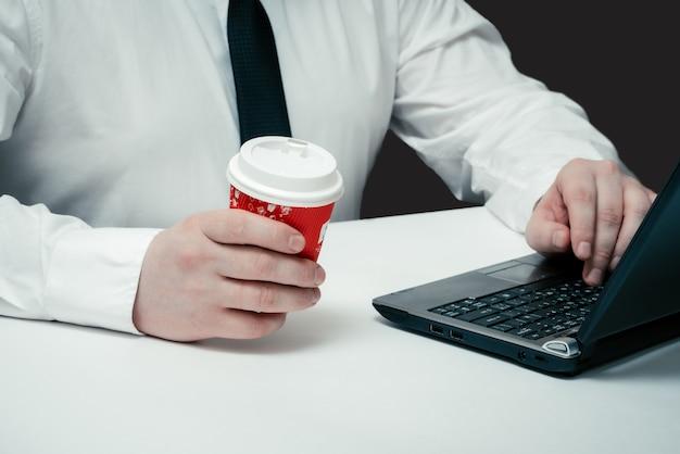 ノートパソコンに座って、彼の手でコーヒーの赤いガラスを保持しているサラリーマン
