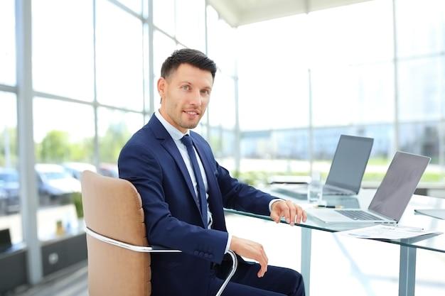 열린 노트북 앞에 사무실에서 책상에 앉아 회사원
