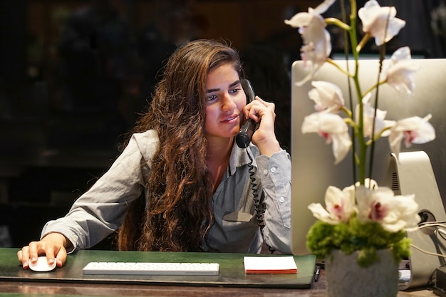 회사원은 직장에서 전화로 말합니다. 여성 에이전트 여행사 체크 아웃