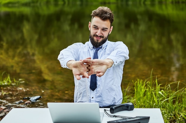 An office worker stretches while sitting at  table on which are  laptop and  landline phone, behind  white collar is  natural landscape with river water.