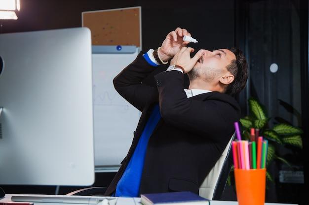 Office worker suffering dry eye syndrome, artificial tears eye drops