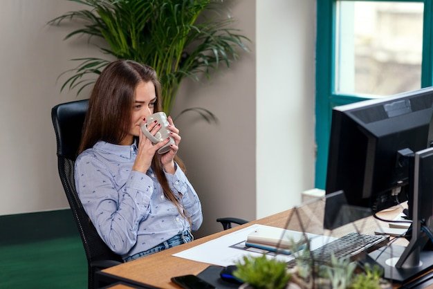 Office worker taking a coffee break with a cup of espresso in her hands.